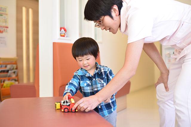 お子さんとおもちゃで楽しく遊ぶスタッフ
